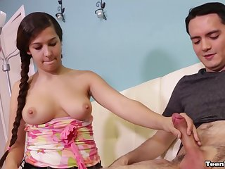 Bashful young miss with long braided pigtails sheepishly gives a handjob